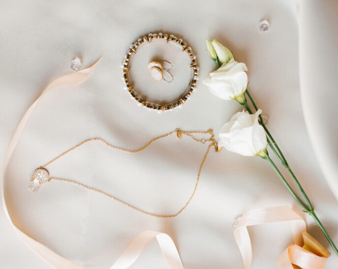 bride's wedding accessories: bracelet, earrings, chain with pendant and eustoma flowers on beige background