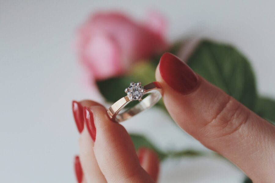 A closeup shot of a female holding a gold diamond ring with a pink rose in a blurred background