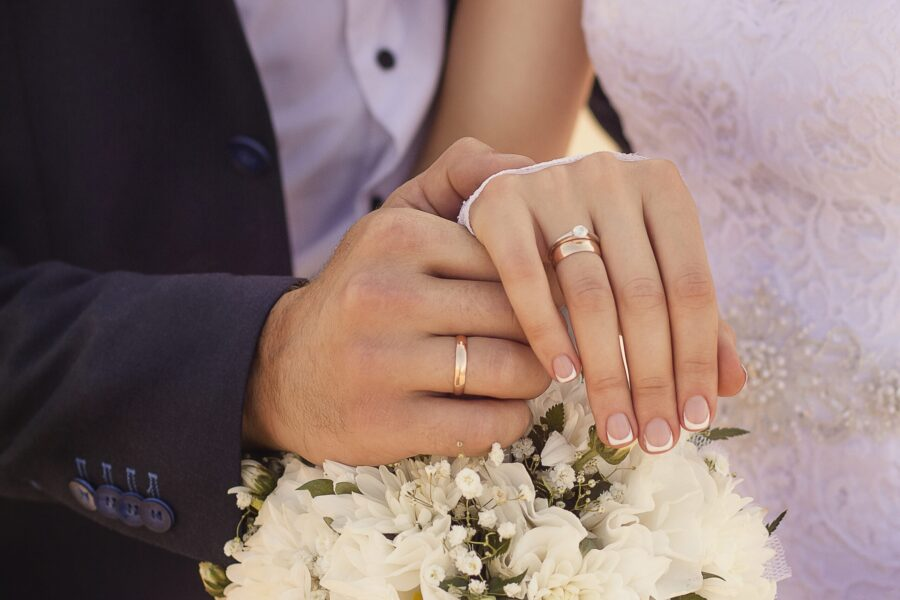 A closeup shot of newlyweds holding hands and showing the wedding rings