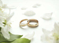 Wedding ring. On a white background and with delicate white flowers. Wedding symbols and attributes